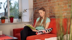 Absorbed girl sitting on the sofa in the living room and doing notes in her jour Stock Footage