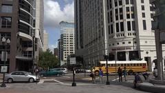 School buses cross Orange Avenue, Orlando, Florida USA Stock Footage