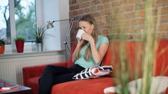 Girl looks calm while talking on cellphone and drinking tea in the living room Stock Footage