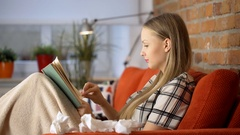 Girl looks very ill while sitting under blanket on the sofa and reading book Stock Footage