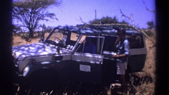 1969: passenger speaks to standing man drinking by open jeep doors parked by Stock Footage
