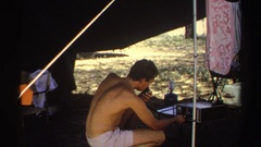 1969: man in tent messing with a machine next to a car SUDAN Stock Footage