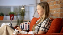 Girl looks unwell and feels sick while sitting on the sofa under blanket Stock Footage
