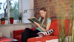 Girl answers cellphone while reading book on the sofa in the living room Stock Footage