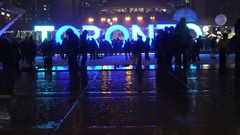 Silhouette of ice skaters at Nathan Phillip's Square on a rainy night  Stock Footage