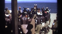 1969: a group of people dancing in a circle near the shore line on a sunny day Stock Footage