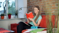 Girl learning notes by heart and drinking tea in the living room Stock Footage
