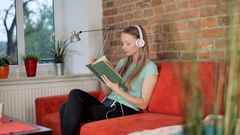Satisfied girl listening music on headphones while reading book Stock Footage