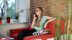 Girl looking happy while chatting on cellphone in the living room Stock Footage