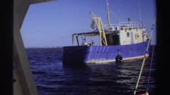 1969: from vantage of boat, another fishing vessel moves away; man on boat with Stock Footage