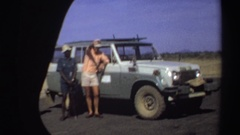 1969: three men standing by a jeep, one waving, as seen from the vantage of a Stock Footage