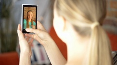 Girl having a videchat with her friend on a smartphone Stock Footage