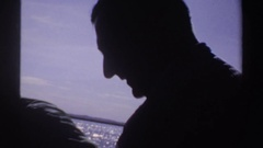 1969: dimly lit people move in front of a brightly lit seascape, one turning to Stock Footage