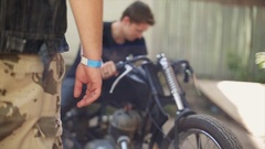 Young man in shirt at self made motorbike. Many different unusual details Stock Footage