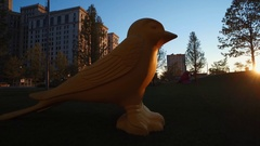 CLEVELAND,  OVERSIZED YELLOW BIRD OUTDOOR STATUE, DOWNTOWN, WITH SUNSET Stock Footage