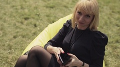 Blonde girl in black dress sit on yellow beanbag on green grass, posing on Stock Footage