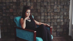 Sexy wistful brunette woman posing sitting in the armchair Stock Footage