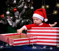 Baby in santa outfit sitting inside a wrapped gift box Stock Photos