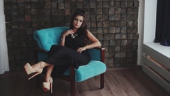 Young pretty wistful brunette woman posing sitting in the armchair Stock Footage
