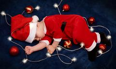 Overhead of baby sleeping in santa outfit with fairy lights Stock Photos