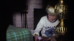 1975: an eager child unwraps a present FLORIDA Stock Footage