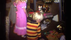 1975: a young boy and girl inspect their unopened gifts on christmas morning Stock Footage