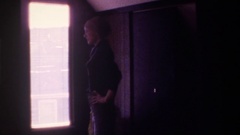 1975: short haired woman looks out window FLORIDA Stock Footage