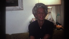 1975: old women chatting inside a house, sitting on a sofa folding clothes Stock Footage