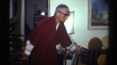 1975: older woman in a christmas sweater helping an elderly man in a red robe to Stock Footage
