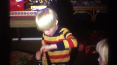1975: golden haired, brightly clothed children open wrapped presents in home Stock Footage