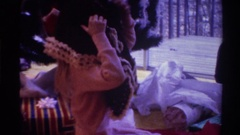 1975: girl tries putting on a poncho and her mother helps while they all sit in Stock Footage