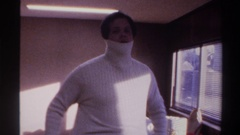 1975: man putting on white turtleneck sweater and dancing for the camera FLORIDA Stock Footage