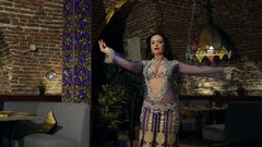 Brunette woman in lilac costume dances belly dance in restaurant Stock Footage