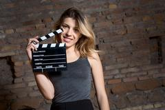 Young blonde actress amazed with movie clapper Stock Photos