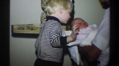 1974: mothers son ecstatic over his newborn sibling, showing his love for the Stock Footage