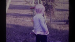 1974: a young child standing and looking around in a playground at dusk FLORIDA Stock Footage