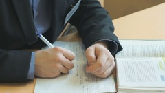 Schoolboy writes text in exercise book on lesson Stock Footage