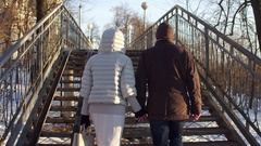 Couple walking holding hands on a small bridge full of love locks. 4K steadicam Stock Footage
