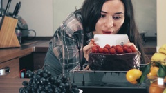 Brunette young woman making photos and videos of her raspberry cake with her Stock Footage