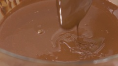 Stirring melted chocolate in a glass bowl close up 4K shot Stock Footage