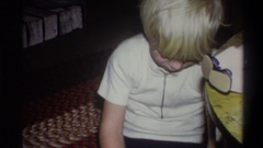 1973: small silver haired boy sitting on the floor and playing with toys NEW Stock Footage