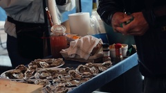 Salesman opening oysters at the seafood market. Real time video Stock Footage