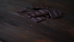 Dark chocolate bar. Cocoa powder in glass cup on wooden background Stock Footage