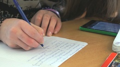 Pupil writes the text on white sheet of paper Stock Footage