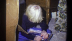 1973: a blond haired boy opens a christmas present while sitting on the living Stock Footage