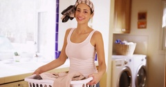 A Hispanic woman does her laundry as she poses for a portrait Stock Footage