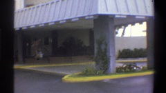1973: hotel awning over a drive through with foliage and greenery, a guest pulls Stock Footage