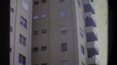 1973: a shaky camera shot of a tall and light brown residential building on a Stock Footage