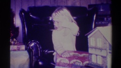 1973: a bleary eyed child begins to open gifts on christmas morning as family Stock Footage