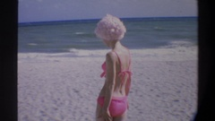 1974: blonde in pink bikini strolls on a beach with her kid FLORIDA Stock Footage